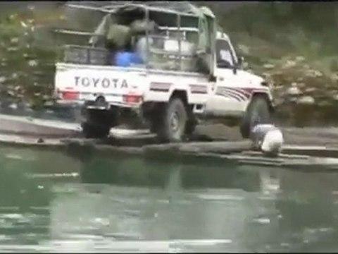 Cruzando camioneta por el rio en canoa