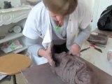 Irène Lahaye sculpte un enfant de terre, à Saint-Amand-les-Eaux