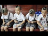 Une mère rase la tête avec des chiffres sur la tête de ses garçons quadruplet
