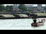 Boats dragging a cargo barge on the Chao Phraya River in Bangkok