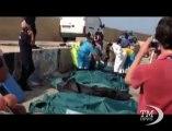 Lampedusa, i corpi dei migranti morti arrivano in porto. I corpi dei migranti allineati sulla banchina