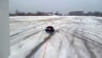 A car pulls a guy lay on the snow! Crazy dumb guy!