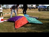 Kite flyers preparing their big colourful kite to launch in the sky