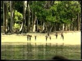 Jarawa kids wave at the boat reaching the shore in Andamans