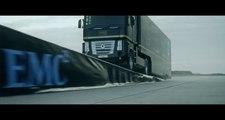 Un camion poids lourd saute au dessus d'une formule 1 pour une pub Lotus F1 Team et EMC