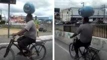 Rouler en vélo avec une bouteille de gaz en équilibre sur la tête