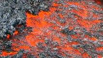 Lava run man runs over glowing lava flow on volcano Etna