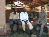 Malawian coffee farmers talking with Engineers Without Borders volunteer about Coffee.