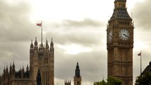Tight shot of Big Ben and Westminster palace with storm clouds in background in London, England.