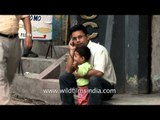 Nepalese upwardly mobile man speaks on phone, with kid in lap