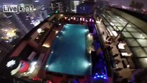 BASE JUMPER jumps off 1,200 ft Kuala Lumpur Tower = lands on pool =