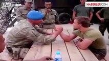 Turkish soldier arm-wrestles vs Dutch soldier.