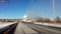 Un camion couvert de neige passe sous un camion et provoque une explosion de poudreuse sur l'autoroute