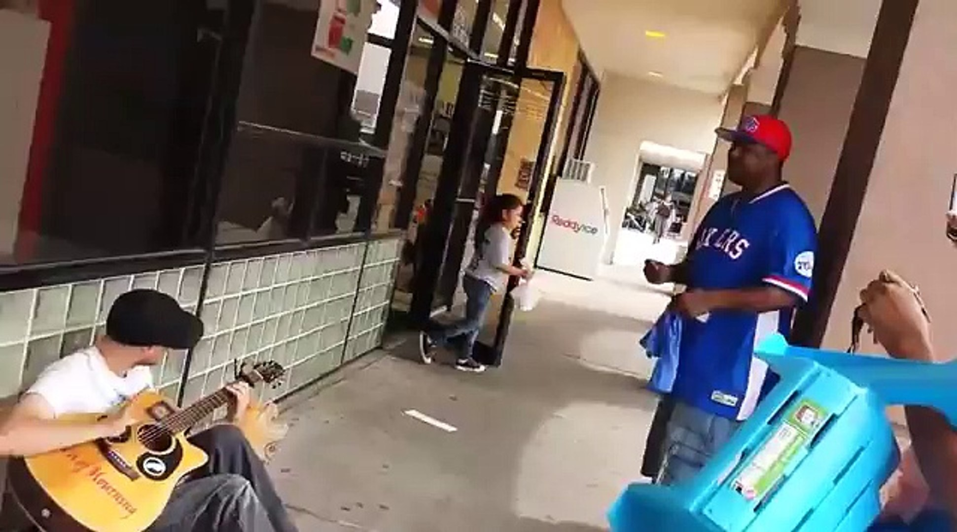 A man films this street musician when a stranger approaches