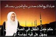 محمد بن عثيمين حكم حمل الطفل في الصلاة إذا كان يجهل هل فيه نجاسة أم لا؟