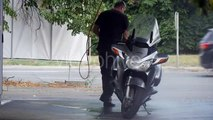 Man With Hosepipe in His Hands Carefully Washes His Silver Motorbike at the Carwash on the