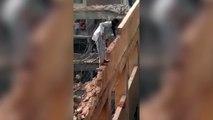 Un ouvrier prend tous les risques pour démolir un bâtiment