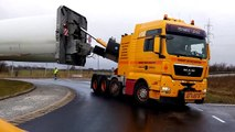 Un camion de 75m de long traverse un rond point transportant une pale d'éolienne
