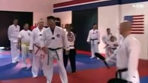Man is Tae Kwon Do green belt   on just one leg