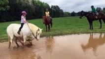 Un poney fait trempette dans une flaque d'eau avec une enfant sur son dos