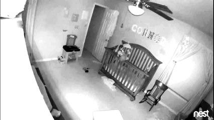 Un bébé tient en équilibre debout sur la barrière de son lit