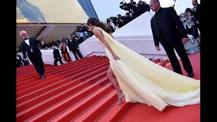 Amal Clooney struggles with her thigh-split gown with George Clooney on the Cannes red carpet
