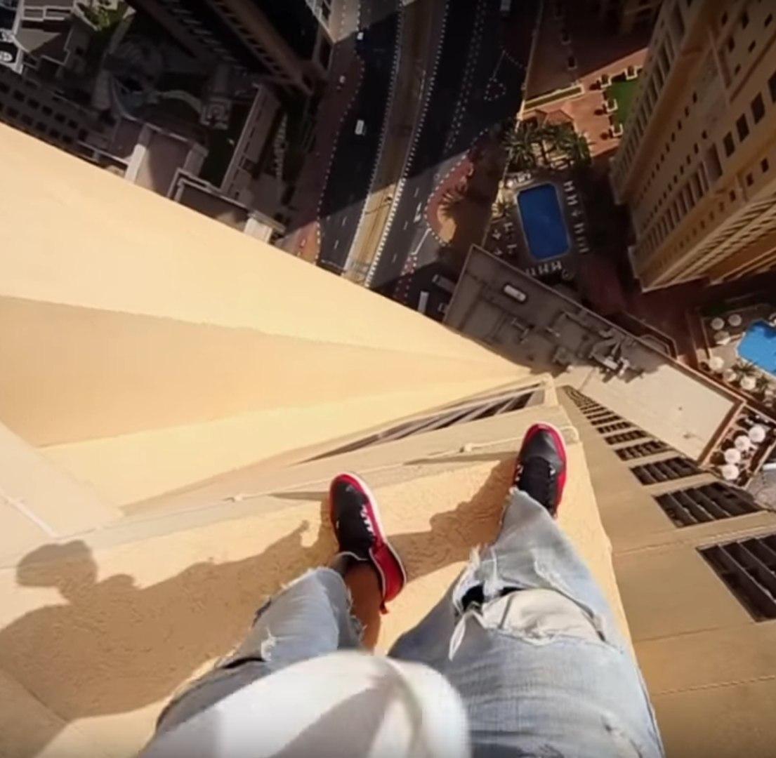 Um homem arrisca a vida pulando da borda de um arranha-céu