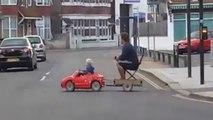Au volant de sa mini-voiture, le petit garçon conduit son père à la maison