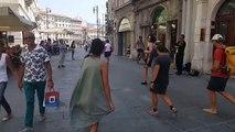 Une jolie fille accompagne un musicien de rue en dansant