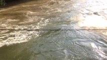 Surfer une rivière en crue en suisse, accroché à un pont