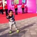 Un enfant chinois répète la chorégraphie des danseuses derrière lui et il danse très bien pour son âge