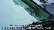 Windscreen wipers on car front glass tearing rain drops, daytime. Stock Footage