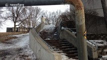 Man attempts to grind handrail on skis, hurts himself