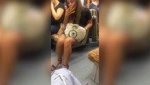 Une fille mange ses spaghettis dans le métro