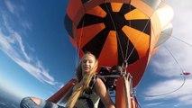 Une nana au déc0lleté généreux se fait un petit saut en parachute d'une montgolfière