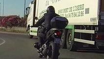 Ce motard prend tout les risques pour doubler un camion dans un rond point.... Gros débile