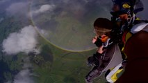 Skydivers soar above 360 degree double rainbow