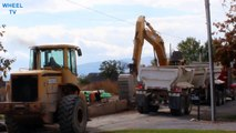 Deere Excavator loading a double dump truck while a Deere loader works nearby on a road construction