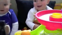 Baby twins having fun with a stuffed animal
