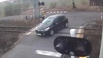 Cette voiture traverse un passage à niveau avec les barrières baissées..