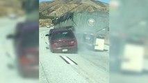 Un camion roule avec une voiture accrochée à sa remorque