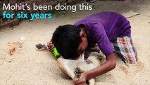 Indian boy drink milk from dog