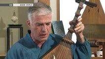 Un homme se demande où il est en regardant son pote jouer de la guitare