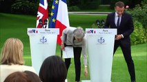 Theresa May loses papers during presser with Emmanuel Macron