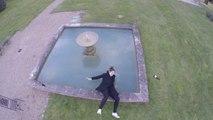Une femme chute dans une fontaine en regardant un drone