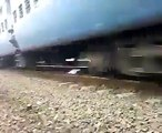 Indian man lying down on the train track and train is passing on it. Very dangerous.
