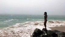 Une fille fait la belle au bord de la mer et finit par se prendre une vague !