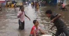 Children Play on Flooded Street as Heavy Rain Prompts School Closures in India