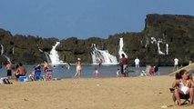 Les familles se baignent comme d'habitude mais quand elles regardent les rochers, tout le monde sort de l'eau