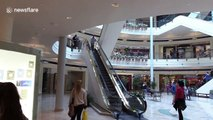 Man in Santa Claus hat descends shopping mall escalator on skis